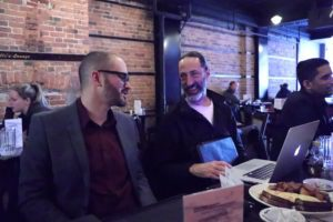 Michael MacMillan and John Kopano seated in front of a laptop in a diner talking about SEO.